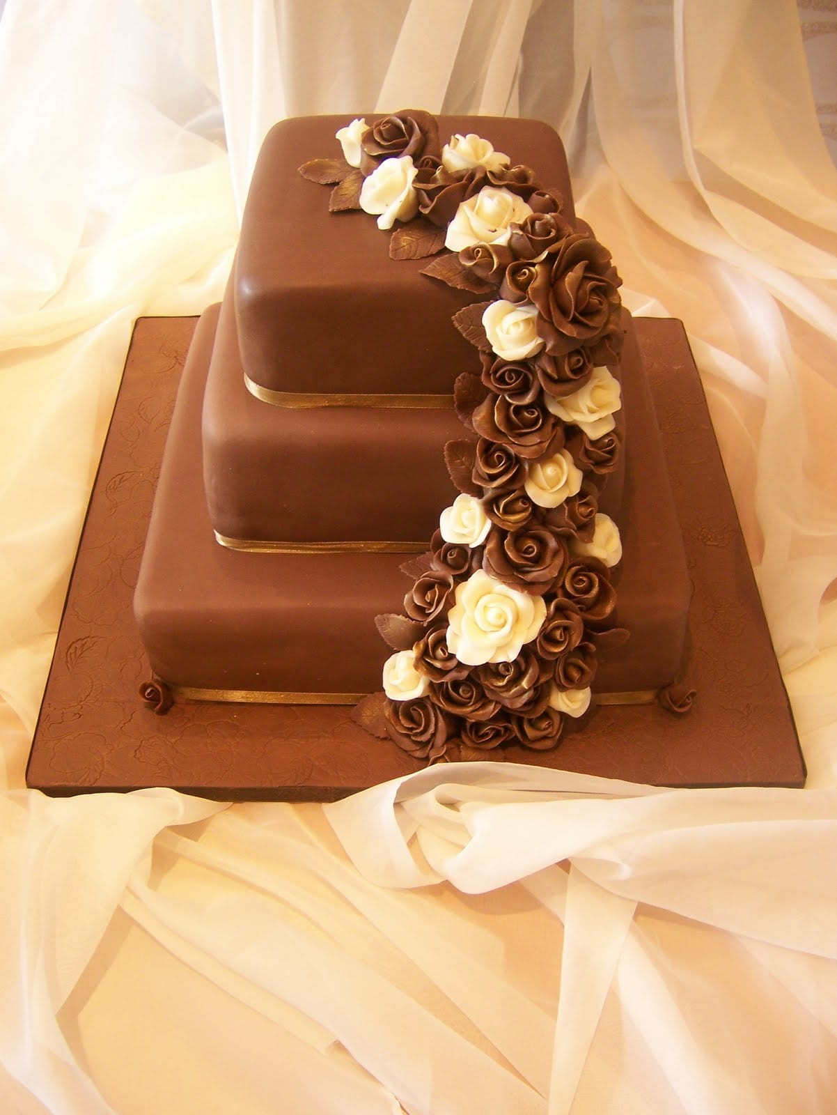 Three tier chocolate wedding cake with cascading roses
