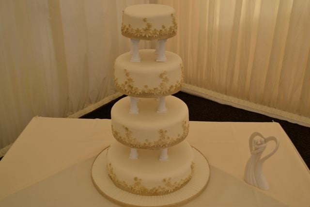 gold wedding cake with pillars