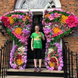 Violet with her 10k medal outside a floral door in Liverpool